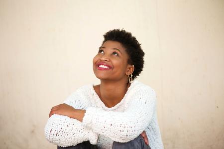 mujer pensativa: Close up retrato de una mujer joven feliz sonriendo y mirando hacia arriba