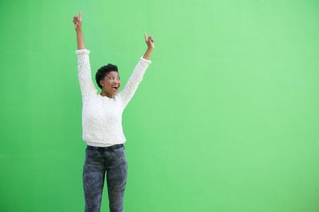 manos levantadas: Retrato de una mujer de raza feliz joven africana que anima con los brazos levantados Foto de archivo