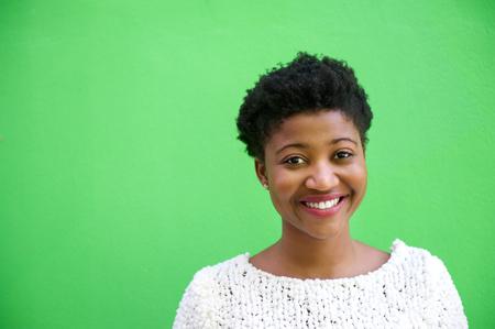 Close-up portret van een lachende jonge Afro-Amerikaanse vrouw die op groene achtergrond Stockfoto