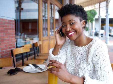 Close up portrait of a smiling woman sitting at outdoor restaurant with mobile phone and drink photo