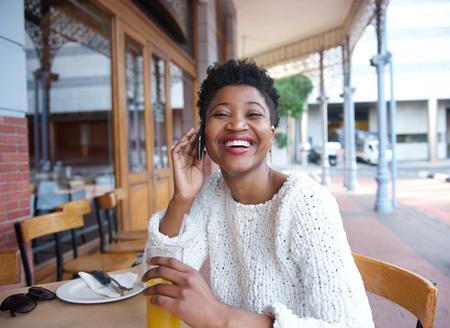 carita feliz: Close up retrato de una mujer joven hablando por tel�fono m�vil en el restaurante Foto de archivo