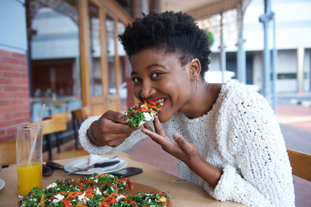 Close up portrait of a young black woman eating vegetarian pizza photo