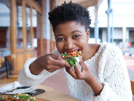 행복 한 아프리카 계 미국인 여자 먹는 피자의 초상화를 닫습니다