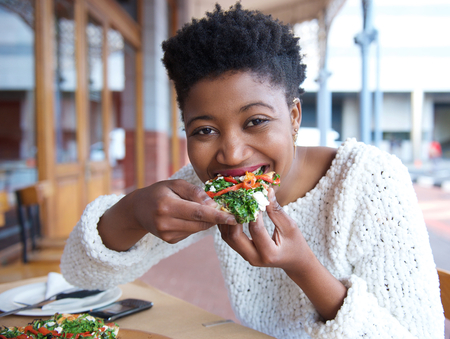 Close up portrait of an happy african american woman eating pizza Imagens