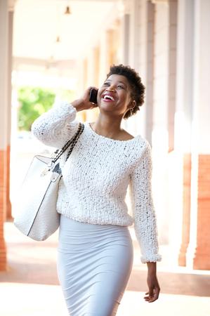 modelos negras: Retrato de un joven africano americano mujer caminando y hablando con el tel�fono celular
