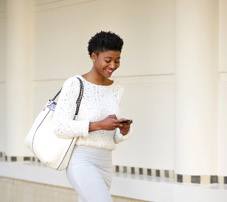 woman holding bag: Close up portrait of a smiling woman sending text message on mobile phone