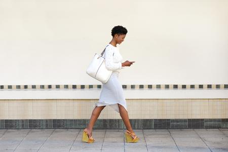 Ganzkörperansicht Seiten Porträt einer jungen Frau zu Fuß und das Senden von SMS-Nachricht auf Handy