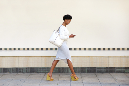 Full length side portrait of a young woman walking and sending text message on cell phone