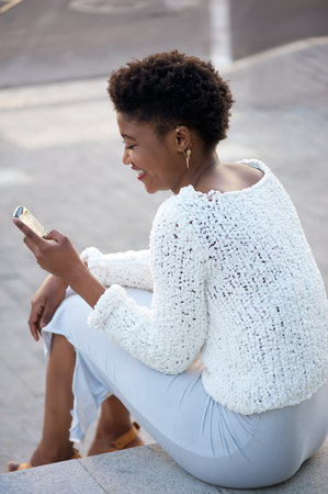 woman behind: Happy young woman sitting down outside sending text message on cellphone