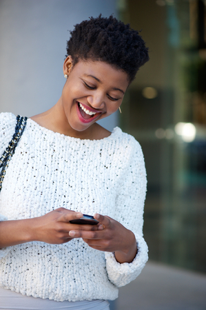 Close up portrait of a young woman laughing and reading text message on cellphone photo