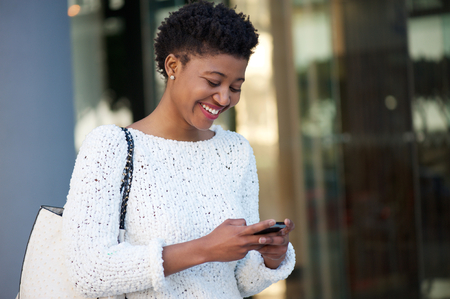Close up portrait of a happy young woman walking in the city sending text message on cellphone