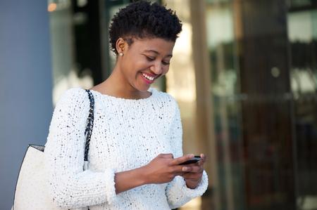 persone nere: Primo piano ritratto di una giovane donna felice a piedi in citt� l'invio di messaggio di testo sul cellulare