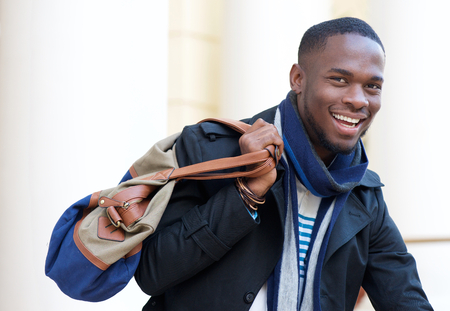 Close up portrait of a happy african american man standing outdoors with bag