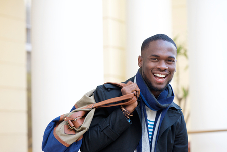 Close up portrait of a happy traveling man standing outdoors with bag Stock Photo