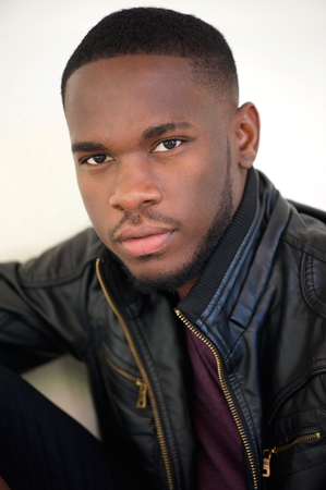 Close up portrait of a handsome african american man posing in black leather jacket photo