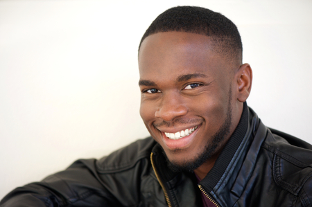 cute man: Close up portrait of a happy young african american man smiling on white background