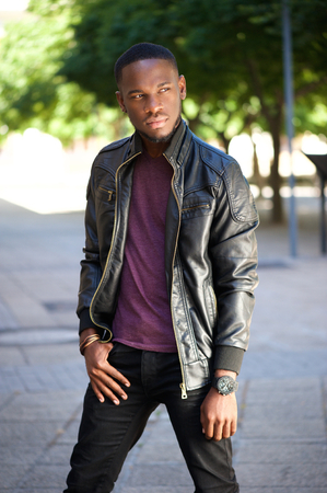 Portrait of a cool black man in leather jacket posing outdoors photo