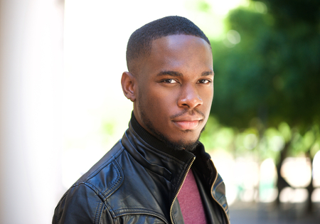 Close up portrait of a handsome young black man posing outside photo