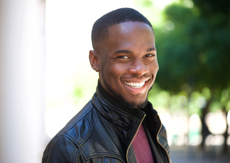 Close up portrait of a cheerful young african american man smiling outside