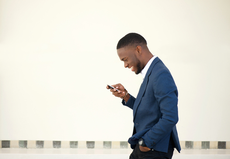 Side portrait of a smiling businessman walking and sending text message on mobile phone Standard-Bild