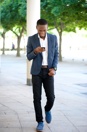 people laughing: Full body portrait of a handsome man walking and sending text message on cellphone Stock Photo