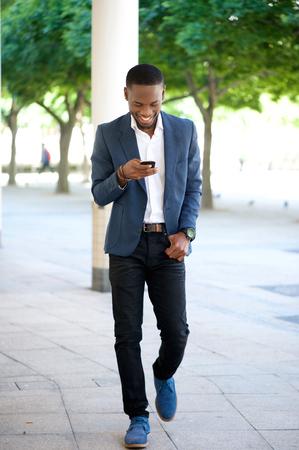 modelos negras: Retrato de cuerpo entero de un hombre caminando guapo y enviar el mensaje de texto en el tel�fono m�vil Foto de archivo
