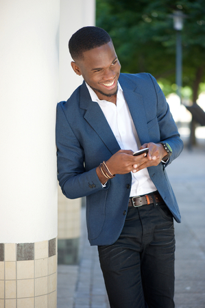 Portrait of a smiling young businessman sending text message by cellphone photo