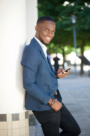 american city: Portrait of a cool young businessman sending text message by mobile phone