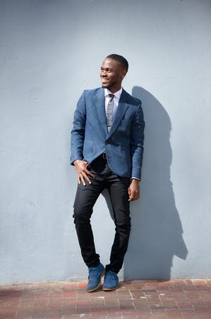 modelos hombres: Retrato de cuerpo entero de un hombre de negocios sonriente de pie contra el fondo gris