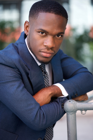 african fashion: Close up portrait of a cool businessman posing outside with arms crossed Stock Photo