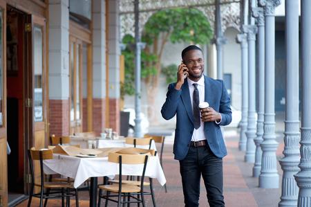 Portrait eines freundlichen Geschäftsmann zu Fuß und im Gespräch über Handy