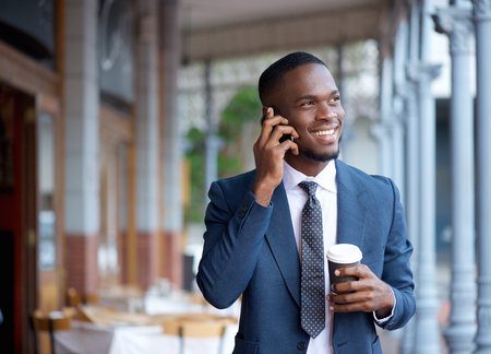 Portrait of a smiling businessman walking and talking on mobile phone photo