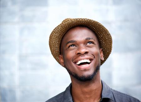 Närbild porträtt av en glad ung man skrattar och tittar upp Stockfoto