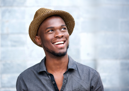 people laughing: Close up portrait of a happy young african american man laughing against gray background