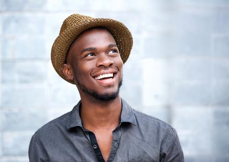 hombres negros: Close up retrato de un joven afroamericano feliz riendo contra el fondo gris Foto de archivo