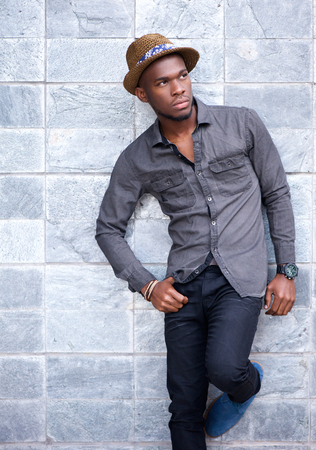 suave: Portrait of a handsome young african american man leaning against wall