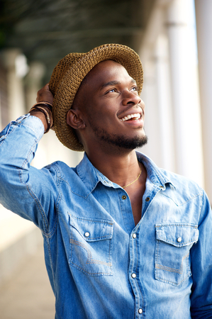 young man jeans: Portrait of a carefree young african american man smiling with hat