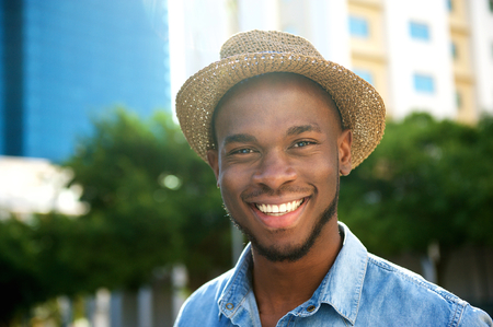 Close up portrait of a trendy young african american man smiling with hat photo