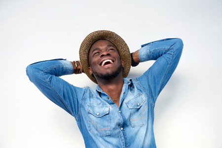 Close up portrait of a young man laughing with hands behind head on white background Stock Photo