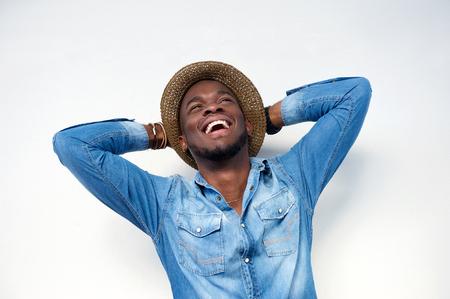 riendo: Close up retrato de un hombre joven de risa con las manos detrás de la cabeza en el fondo blanco Foto de archivo