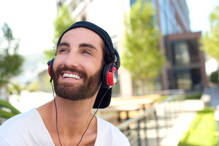 Close up portrait of a handsome young man smiling with headphones photo