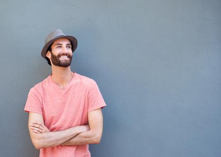 Portrait eines attraktiven jungen Mannes, lächelnd mit gekreuzten Armen auf grauem Hintergrund Standard-Bild - 36640766