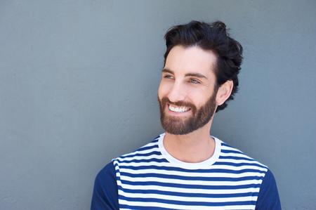 beau jeune homme: Close up portrait d'un beau jeune homme avec une barbe en souriant sur fond gris Banque d'images
