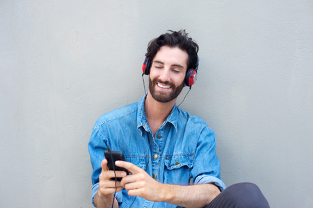Portrait of a handsome young man smiling with mobile phone and headphones photo