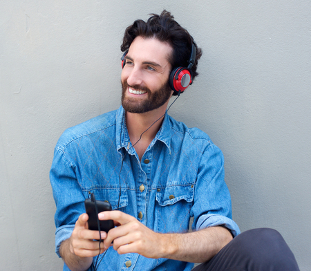 Portrait of a happy man sitting with headphones and mobile phone Stock Photo