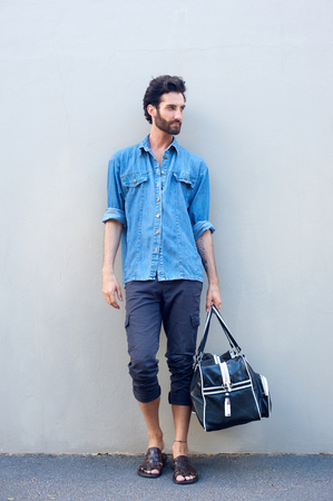 Full body portrait of a male fashion model with beard holding a travel bag on gray background Stock Photo - 36673271