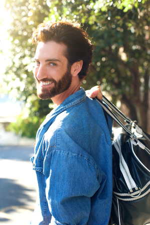man behind: Portrait of a handsome young traveling man smiling with bag