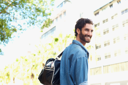 male fashion: Portrait of a happy young man traveling with bag outdoors