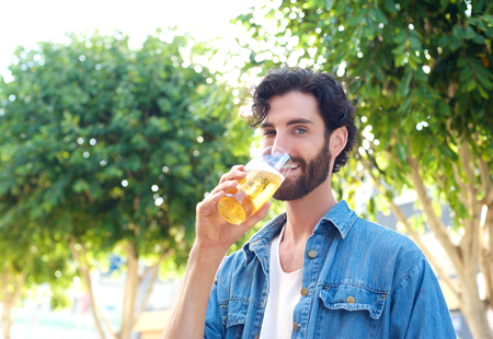 refreshing: Young man with beard enjoying a cool refreshing  beer at and outdoor bar in summer