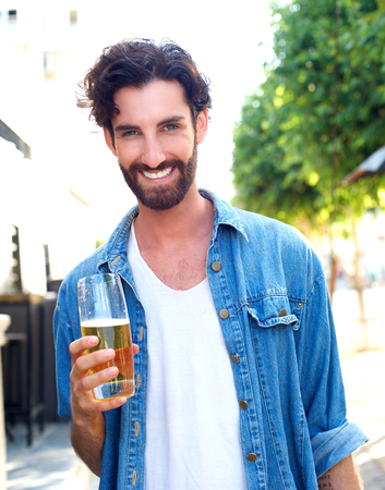 single beer: Portrait of a smiling young man in blue shirt holding glass of beer